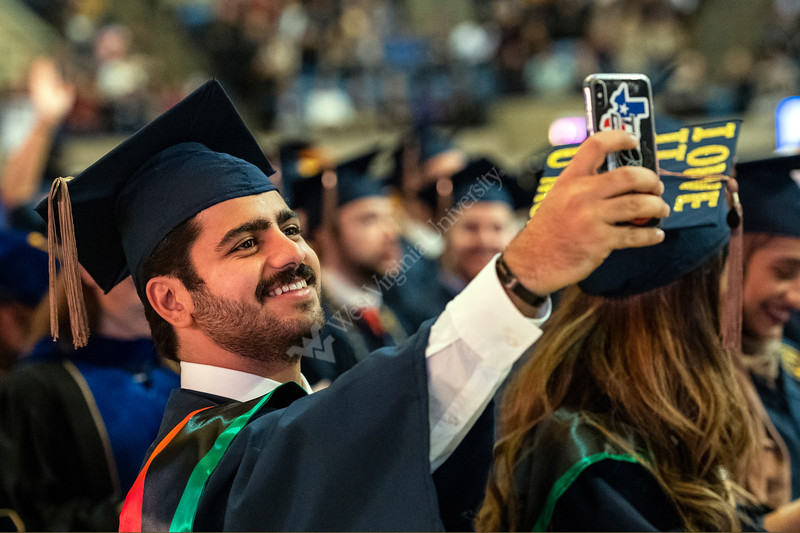 Mohammad Al Thaker Finance major face times with his family in Kuwait at the  Eberly College of Arts and Science and the John Chambers College of Business and Economics December 2018 Commencement at the WVU Coliseum , December 12, 2018. Photo Greg Ellis