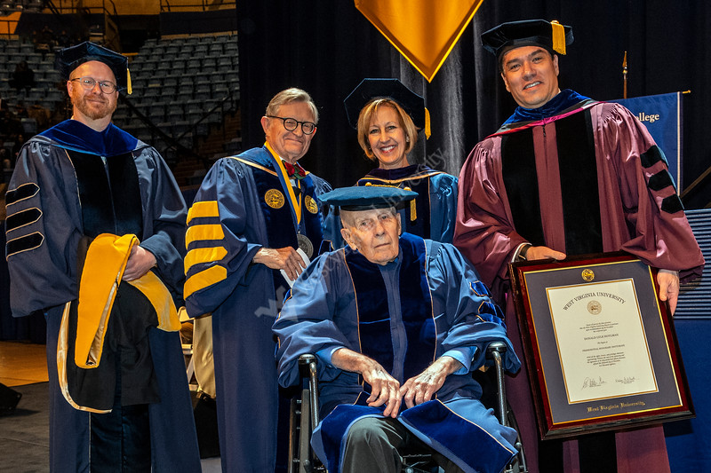 Donald Hoylman, founder of Industrial Resources, Inc. of Fairmont WV receives an HDR  from WVU President E. Gordon Gee (R) and Dean Javier Reyes (L) at the 2018 Eberly College of Arts and Science and the John Chambers College of Business and Economics December 2018 Commencement at the WVU Coliseum , December 12, 2018. Photo Greg Ellis