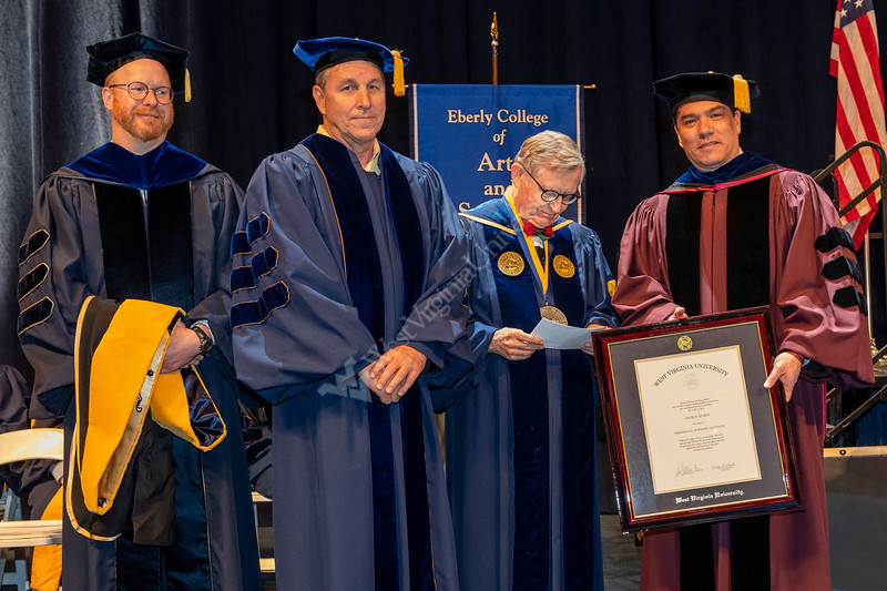 Jack Furst, a distinguished private equity investor and adjunct professor at The University of North Texas receives an HDR  from WVU President E.Gordon Gee (L) and Dean Javier Reyes (L) at the 2018 Eberly College of Arts and Science and the John Chambers College of Business and Economics December 2018 Commencement at the WVU Coliseum , December 12, 2018. Photo Greg Ellis