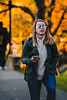 A student with mirror shades walks through campus on a fall evening.