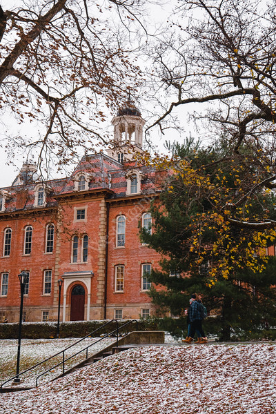 Two students walk past Martin Hall on a cold, snowy day.
