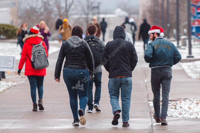 A student gets into the festive spirit early as he walks with friends across the Evansdale campus.