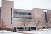 A student walks past the Mineral Resources Buildling on a snowy day.