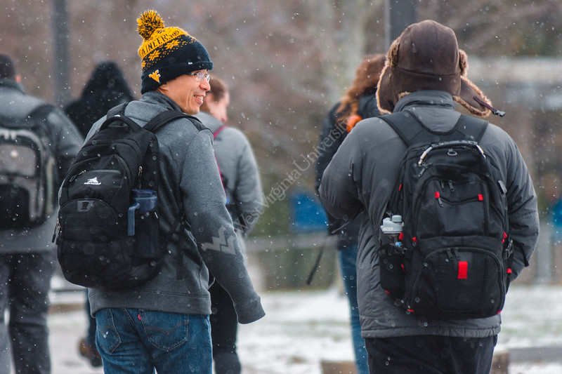 Two students share a joke on the way to class on a wintery day.