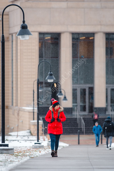 A student braces the cold walking across the Evansdale campus.