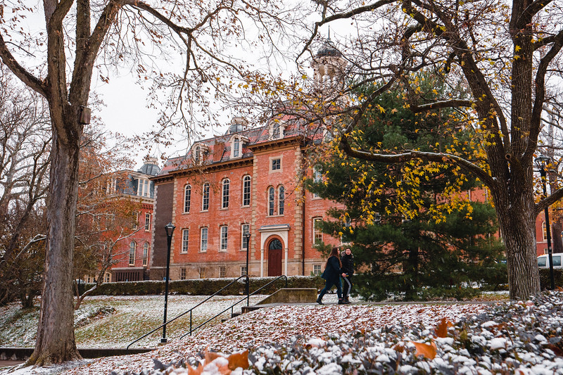 Two students walk past Martin Hall on a snowy day.