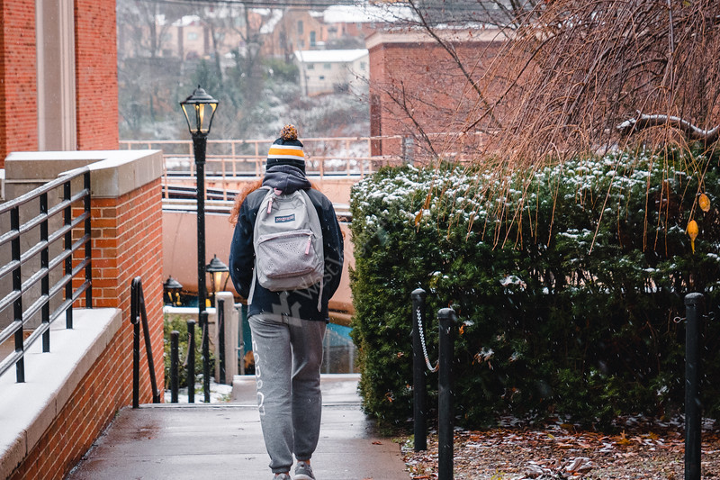 A student braces the cold as they walk to class.
