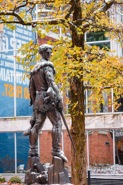 The Mountaineer statue with a light dusting of snow with fall leaves in the background.