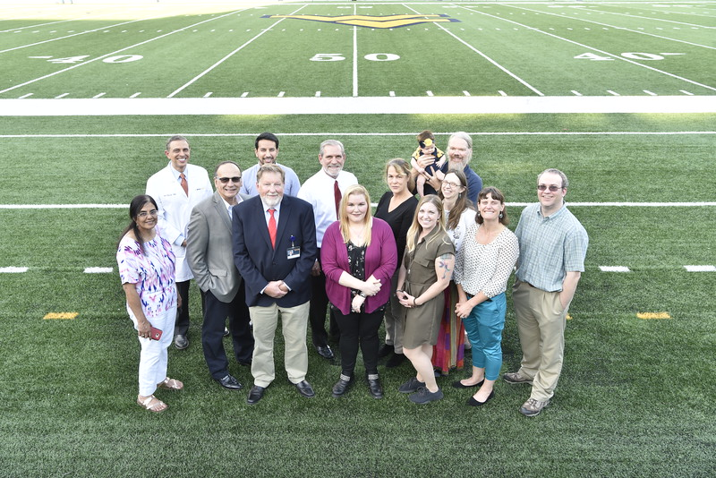 Rockefeller Neuroscience Institute doctors researchers an and staff pose for photos at Mountaineer Field October 1, 2018. Photo Greg Ellis