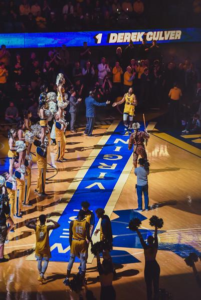 Derek Culver high fives a coach as he runs down the carpet ahead of the men's basketball game against K-State.