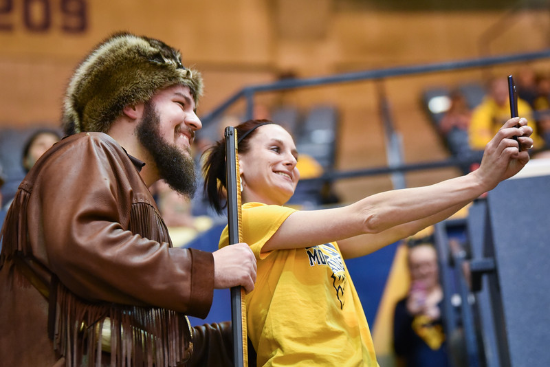 Mascot finalist Thaiddeus Dillie takes a selfie with a fan during the second half of the WVU men's basketball game against K-State.