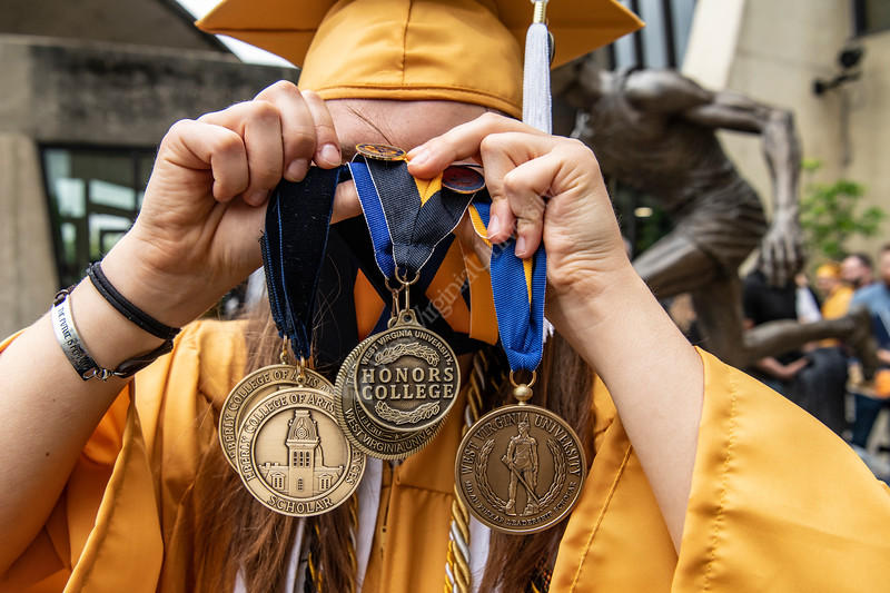 Truman Scholar Emma Harrison displays her medallians at the conclusion of the Eberly College of Arts and Sciences Undergraduate Commencement at the Coliseum May 12th, 2019.  Photo Brian Persinger