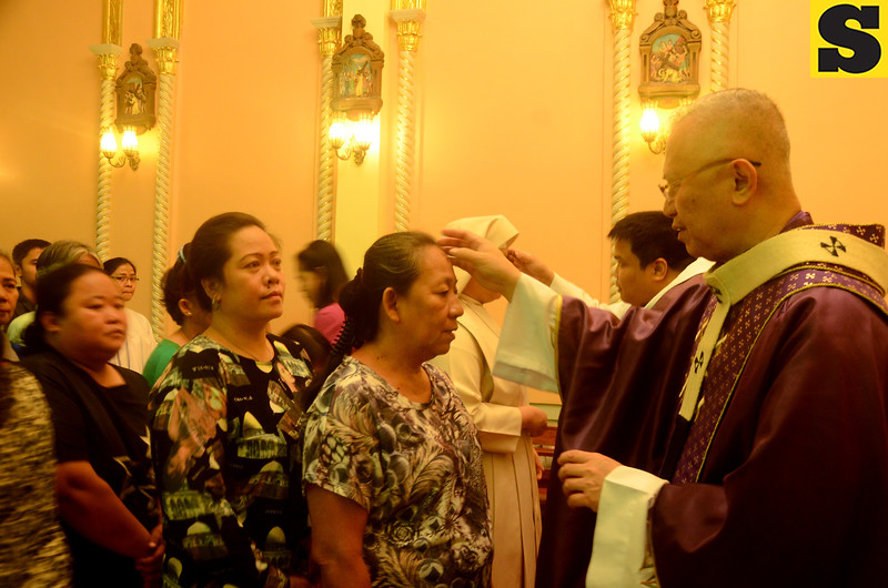 Cebu Archbishop Jose Palma marks the forehead of the faithful who attended the Ash Wednesday mass