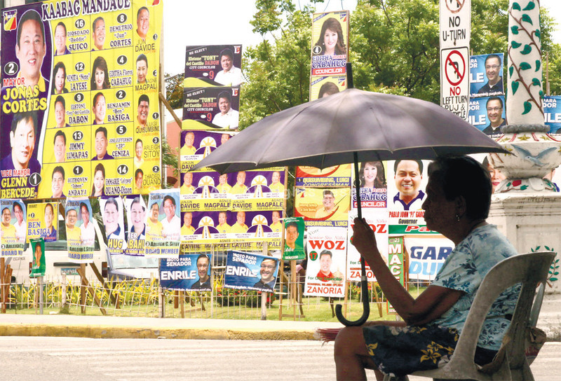 WRITING ON THE WALL. A common poster area in Mandaue City, right in front of the National Shrine of St. Joseph, gives passersby and this woman peddling candles a menu of candidates to choose from. (Allan Cuizon)
