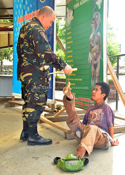 DAVAO. Anthony Quijano stares at Jessie dela Peña of Task Force Davao who hands him a suman through his right foot at the entrance of the Davao Overland Transport Terminal on Sunday. (Seth delos Reyes)