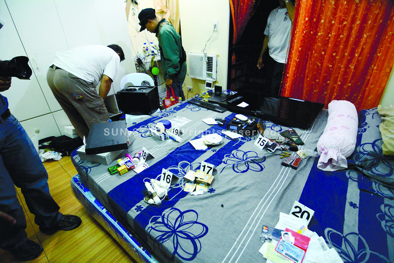 A CYBERSEX DEN IN LABANGON? A National Bureau of Investigation (NBI) team rounds up evidence in an alleged base for cybersex operations in Barangay Labangon, Cebu City.  (Alex Badayos)