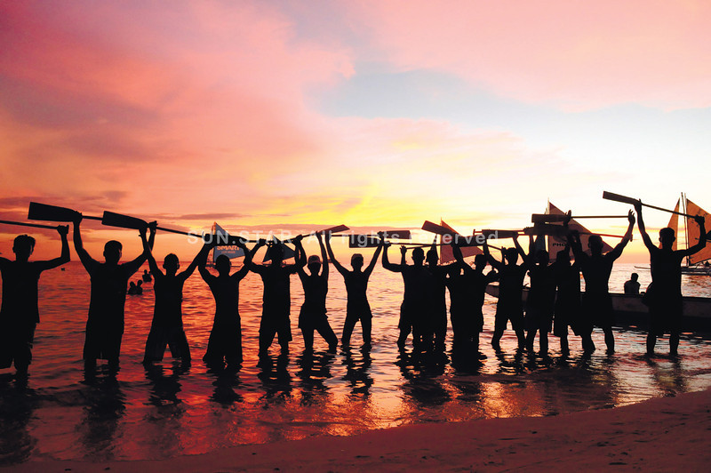 PADDLERS IN BORACAY. Sea Dragon paddlers pose during a beautiful sunset in Boracay, which has been known for its pristine white sands. (Allan Defensor of Sun.Star Cebu)