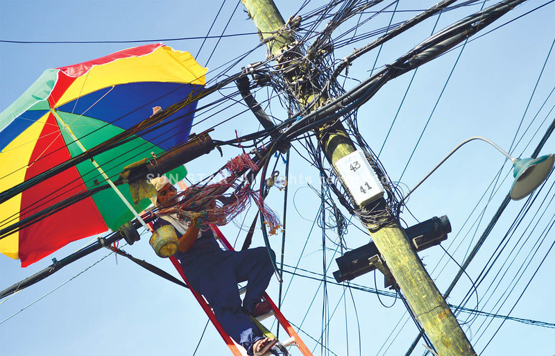 CEBU. A lineman takes cover under an umbrella while working in the midday heat. (Alan Tangcawan)