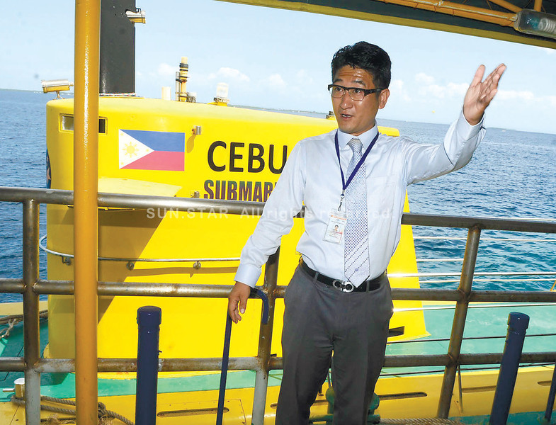 SUBMARINE TOUR. Cebu Yellow Submarine general manager Jun Kim briefs guests before<br /> boarding the submarine (background) at the Imperial Palace Waterpark Resort and Spa in<br /> Lapu-Lapu City. Said to be the first tourist submarine in the country, the Cebu Yellow Submarine can accommodate up to 48 passengers at a time. (Arni Aclao)