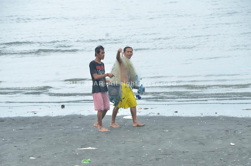 Gipakita sa lalaki nga duna silay kuha nga isda sa ilang pagpamaling sa dagat dapit sa Magsaysay Park, siyudad sa Davao kagahapon sa udto. (Seth delos Reyes)