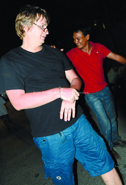 A CYBERSEX DEN IN LABANGON? A National Bureau of Investigation (NBI) team rounds up evidence in an alleged base for cybersex operations and arrests a foreigner, Drew Frederick Shobbrook (in black shirt and blue shorts), in Barangay Labangon, Cebu City. Shobbrook says he didn't do anything illegal. (Alex Badayos)