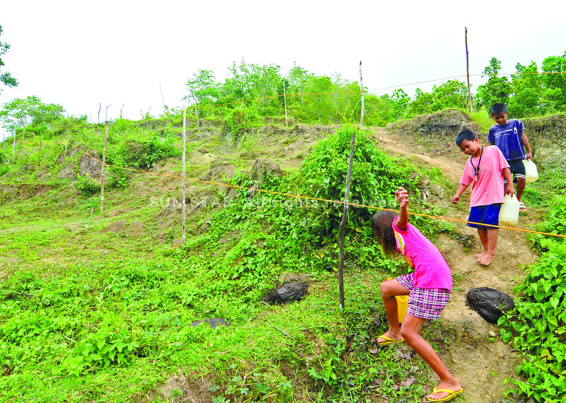 Children in Brgy. Anonang, Inabanga, Bohol fetch water passingby the perimeter fench p0laced by the government at the fault line. Problem of water in the area  after the earthquake last 6 month ago. <br /> foto: Alex Badayos