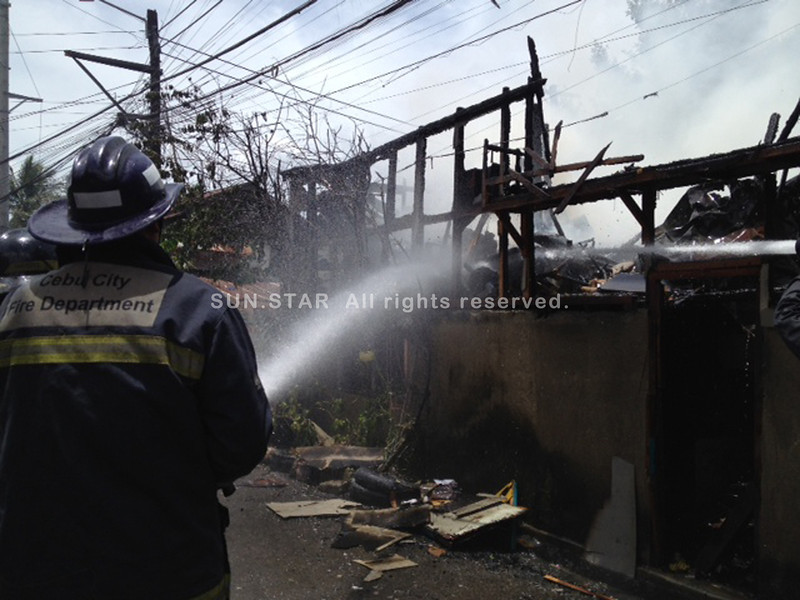 CEBU. A fireman is tyring to put out the fire on MOnday that razed three houses and damaged three others in Barangay Hipodromo, Cebu City. (Ariel Catubig)