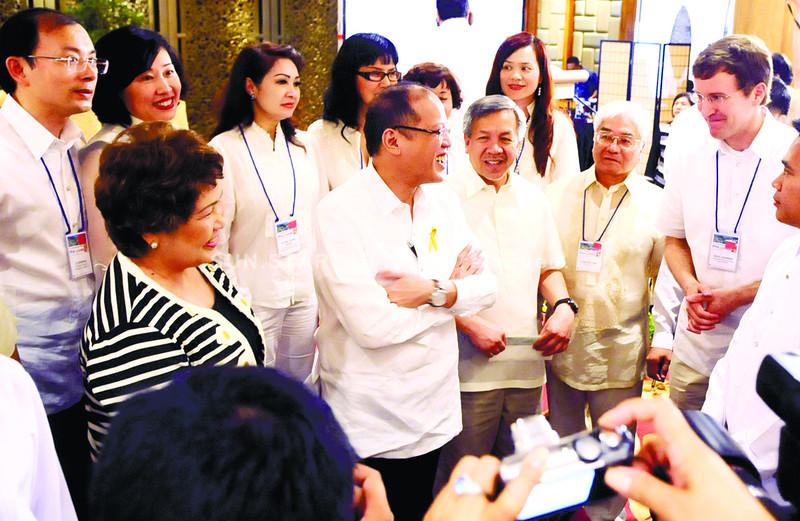 CEBU. President Benigno Aquino III mingles with some delegates of the World Electronics Forum at the Shangri-La Mactan Island Resort and Spa. He is flanked by Trade Secretary Gregory Domingo (to his left) and Lapu-Lapu City Mayor Paz Radaza. (Allan Cuizon)