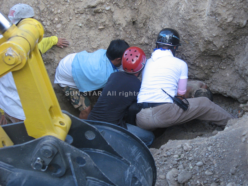 ZAMBOANGA. Rescuers, aided by two back hoes, pull the remains of Miguel Gamorez, one of two construction workers, who died Tuesday when the side of the hill where they were working collapses. (Bong Garcia)