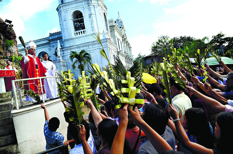 "A CELEBRATION WITH PALMS.  Cebu Archbishop Jose Palma blesses the palms in front of the grotto of the Cebu Metropolitan Cathedral, before the start of Palm Sunday mass. He reminded Christians to try, during Holy Week, to ""enter more deeply into the mysteries of faith.""  (SUN.STAR FOTO/AMPER CAMPAÑA)"