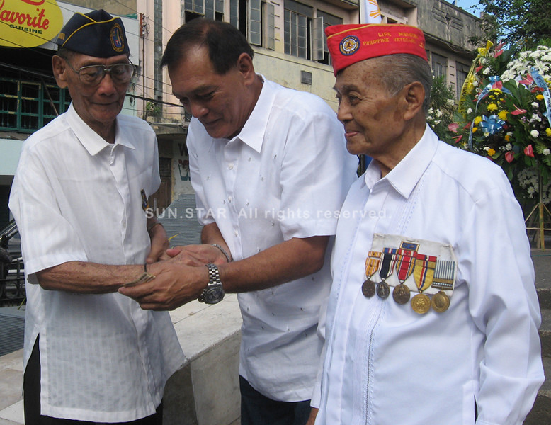 ZAMBOANGA. Mayor Celso Lobregat gives P5,000 cash incentives each to two oldest surviving World War II veterans, namely (left) Aquilino Calandria, 90, and (right) Medardo Jamiro, 89. (Bong Garcia)
