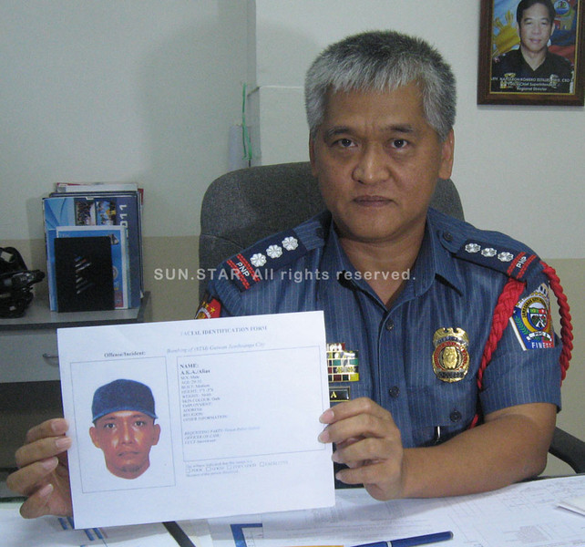 ZAMBOANGA. Police OIC Senior Superintendent James Mejia shows on Monday the computer-generated artist sketch of one of the bombings suspects. (Bong Garcia)