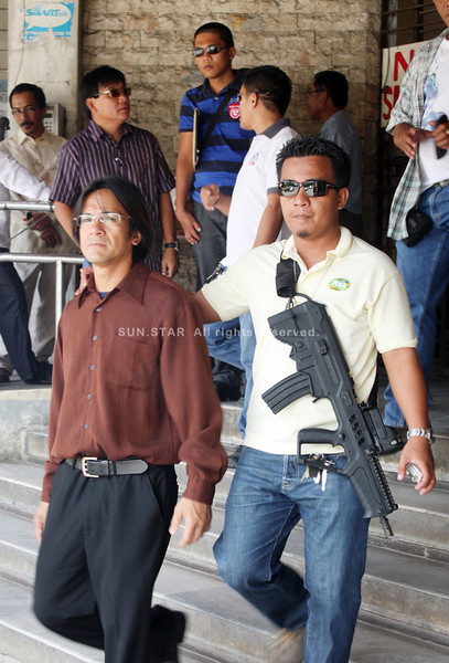 CAGAYAN DE ORO. Controversial car dealer Allan Lynard Bigcas is being escorted by an agent of Philippine Drug Enforcement Agency (PDEA) outside the Hall of Justice after posting P320,000 bail on Monday. Bigcas was caught in possession of illegal drugs, illegal possession of firearms and ammunitions, and possession of illegal drug paraphernalia last Aug. 4. (Joey P. Nacalaban)