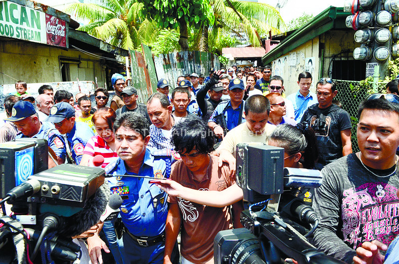 "CEBU. Paul ""JunJun"" Guigue is led away from Barangay Apas by Cebu City Police Chief Melvin Ramon Buenafe (left), who convinced him to let his hostage, a neighbor's child, go unharmed. (Amper Campana)"
