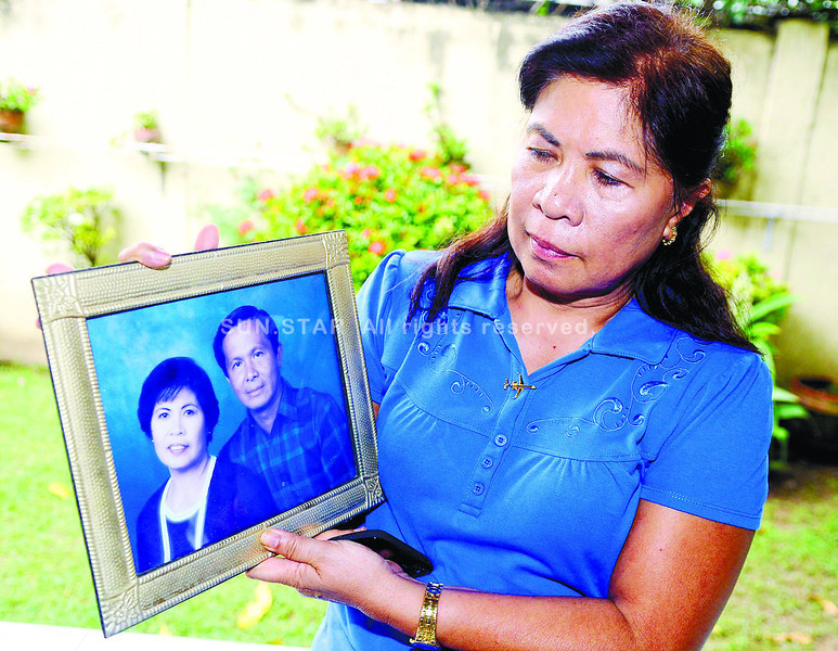 CAPTAIN. Margarita Bahinting shows a framed photograph of her and her husband, Capt. Jessup Bahinting, in their Talisay City home. She remains hopeful for good news and adds she has faith that God has a purpose for all things.  (Sun.Star Photo/Arni Aclao)