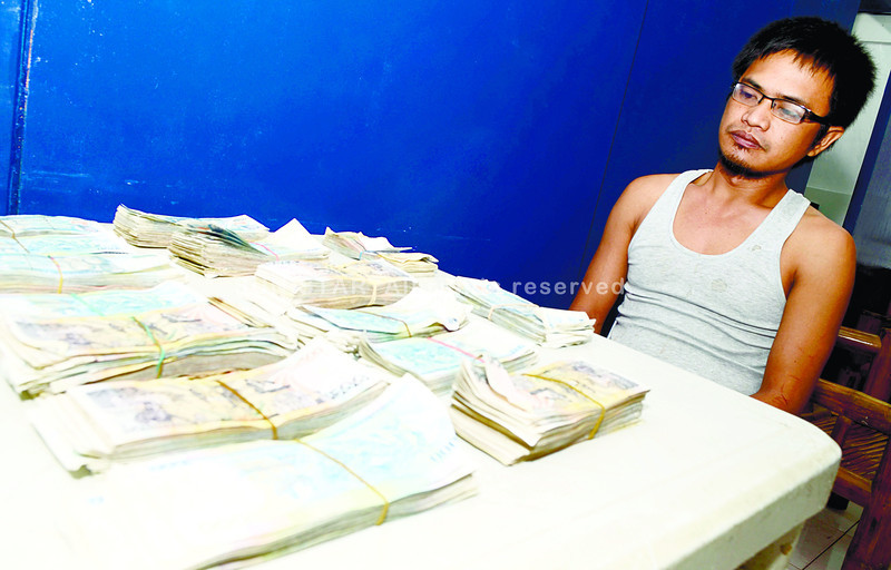 CEBU. Former Pagcor internal security officer Pascual Urian Jr. surrenders to the police the P1.4 million (out of P2.8 million) he allegedly stole from a casino in Mandaue City. (Amper Campaña)