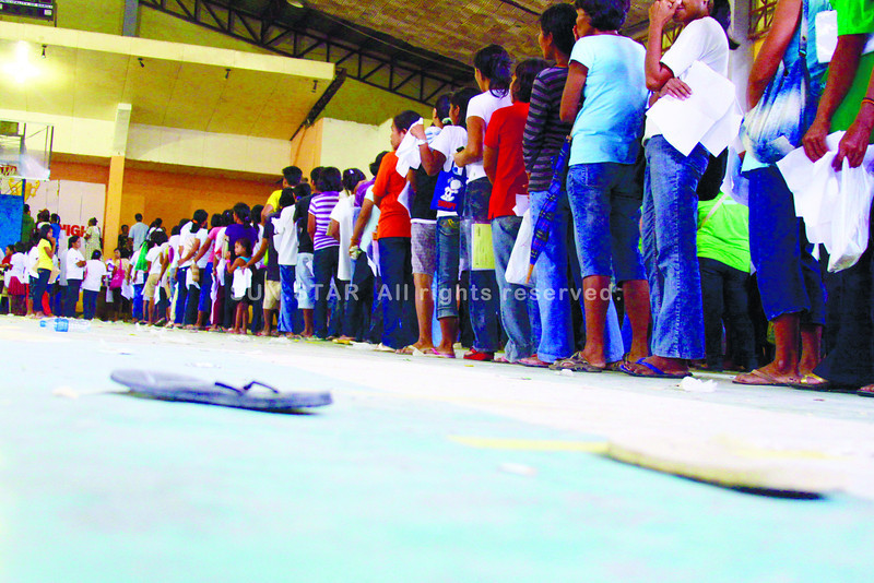 """TRACES OF PANIC.Slippers were left behind during the panic that ensued when an unidentified person shouted, """"There's a bomb!"""" The incident during the distribution of cash to the benificiaries of the Pantawid Pamilya Pilipino Program (4Ps) of President Noynoy Aquino at the Barili Sports Complex. Two women reportedly collapsed during the stampede.(Sun.Star Photo/Alex Badayos)"""