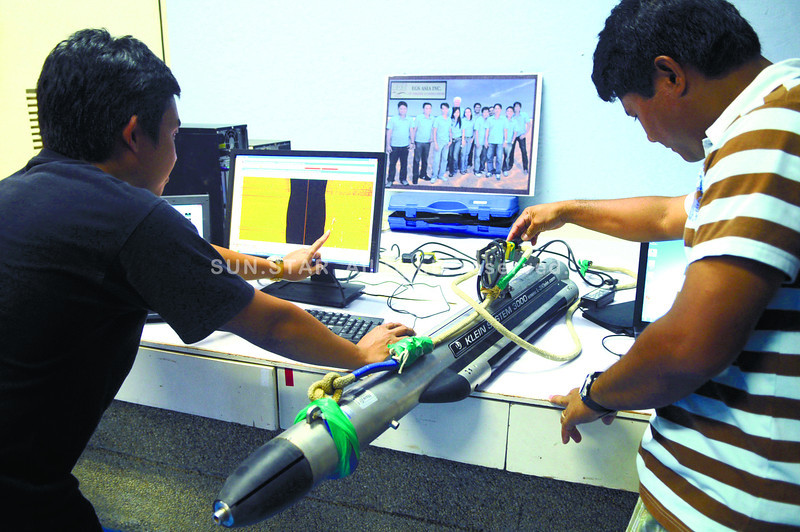 ESSENTIAL EQUIPMENT. Field surveyors Eric Barete (right) and Ralp Ian Abatol of EGS Asia show the side scan sonar that located of the crash site of the aircraft that Local Government Secretary Jesse Robredo rode in. (Sun.Star Photo/Allan Cuizon)