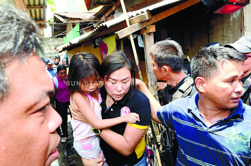 CEBU. A police officer carries the child from the scene. The child, 8, was held hostage by her neighbor on Wednesday, August 29, in Barangay Apas, Cebu City. (Amper Campana)
