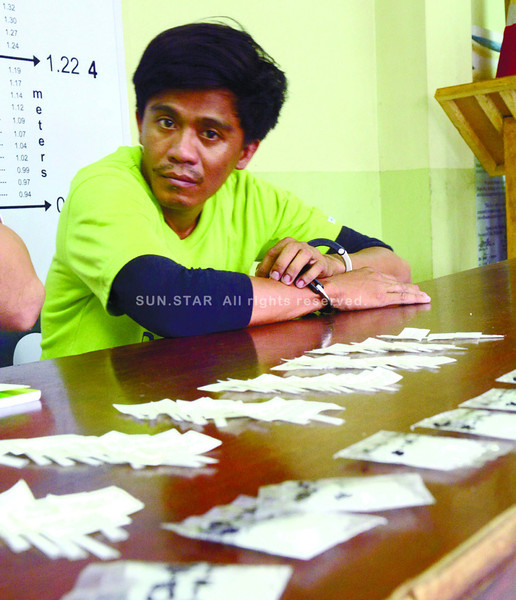 Charlie Barba (right) says he sells shabu but the 10 large packs that the anti-drugs team allegedly found in his house in Barangay Tisa, Cebu City were planted to make him appear that he was a level 2 pusher who could dispose of a large volume of shabu. (Allan Defensor photo/Sun.Star Cebu)