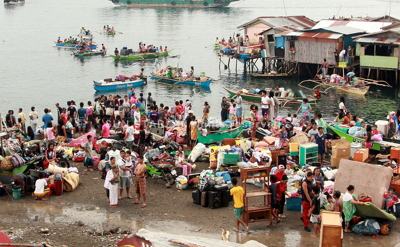 DAVAO. Families affected by the fire in in Sasa scamper near the shores while some even boarded on boats while firemen were trying to put off the fire. (Seth Delos Reyes)