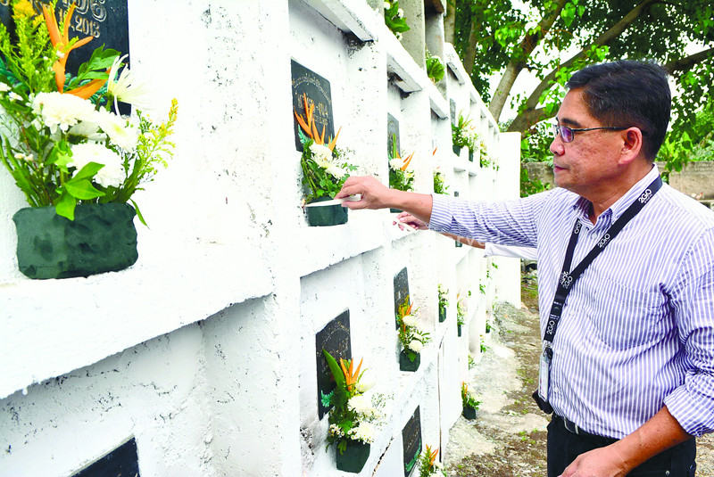 2GO Shipping VP Lito Salvio lighting a candle to the tombs of the victims of M/V Saint Thomas Aquinas of 2GO Group  and M/V Sulpicio Express Siete of Philippine Span Asia Carrier Group collision on the 1st anniversarry of the tragedy that happened last August 16, 2013<br /> <br /> photo Allan Cuizon