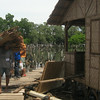 Worker carries nipa roofing materials