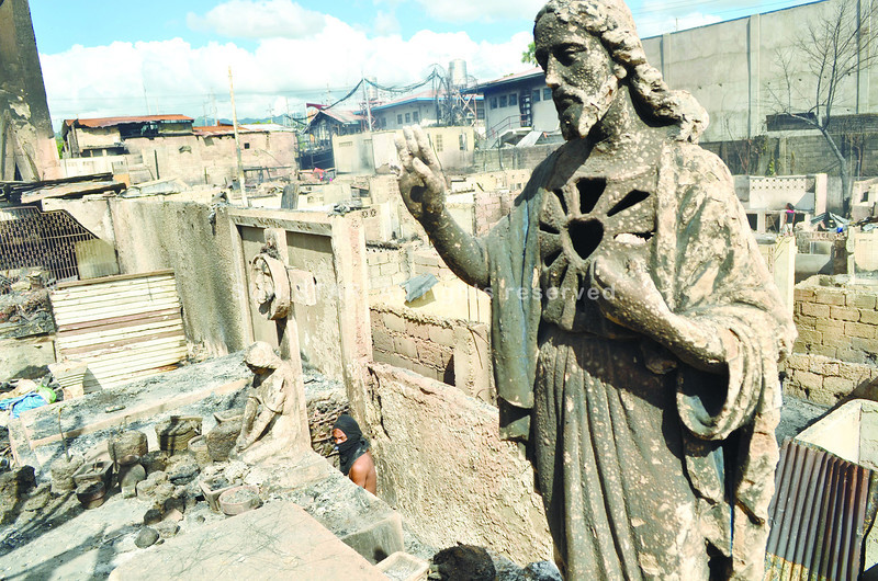 An image of Jesus Christ, placed near a tomb in the Carreta cemetery in Cebu City, towers over the gutted houses in Sitio Laray after a fire that hit two barangays last Tuesday. Another fire before daybreak Wednesday left around 800 more persons homeless, this time in Barangays Kinasang-an and Quiot. (Photo by Amper Campaña of Sun.Star Cebu)