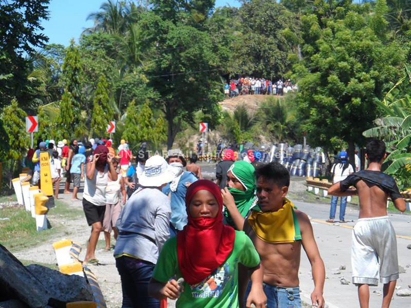 Residents scamper as the police allegedly lobbed the second teargas during the demolition of shanties in Barangay Calangahan in Lugait town, Misamis Oriental. (Contributed photo by STAND IIT)