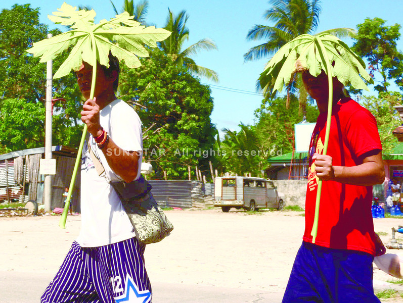 RESOURCEFUL. Two boys go natural in protecting themselves from the sweltering heat of the sun in Yati, Liloan, Cebu. (Photo by Allan Cuizon of Sun.Star Cebu)