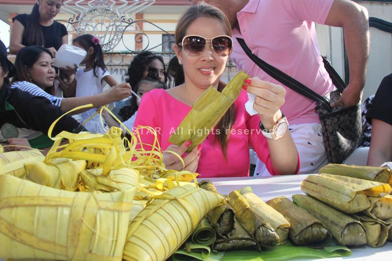 PAMPANGA. Sta. Rita Mayor Yolly Pineda savors the delicious varieties of homemade suman during Sunday's 3rd Suman Festival. (Chris Navarro)