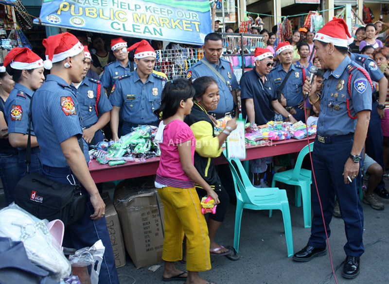 Senior Police Inspector Elmer Robas (far right) leads his other fellow police officers in playing Santa Claus to street kids. (Joey P. Nacalaban)