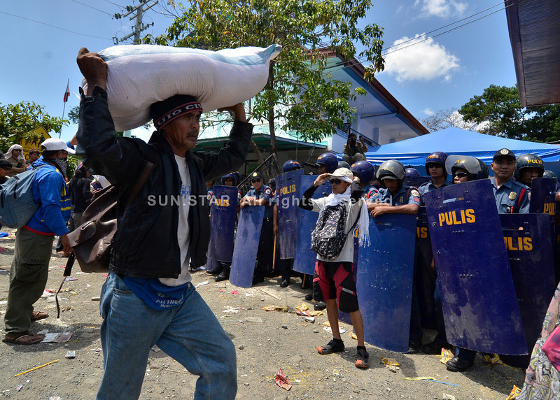 DAVAO. One of the protesters walk past the dispersal team of the Philippine National Police after the ransacking of the Department of Social Welfare and Development office. (King Rodriguez)