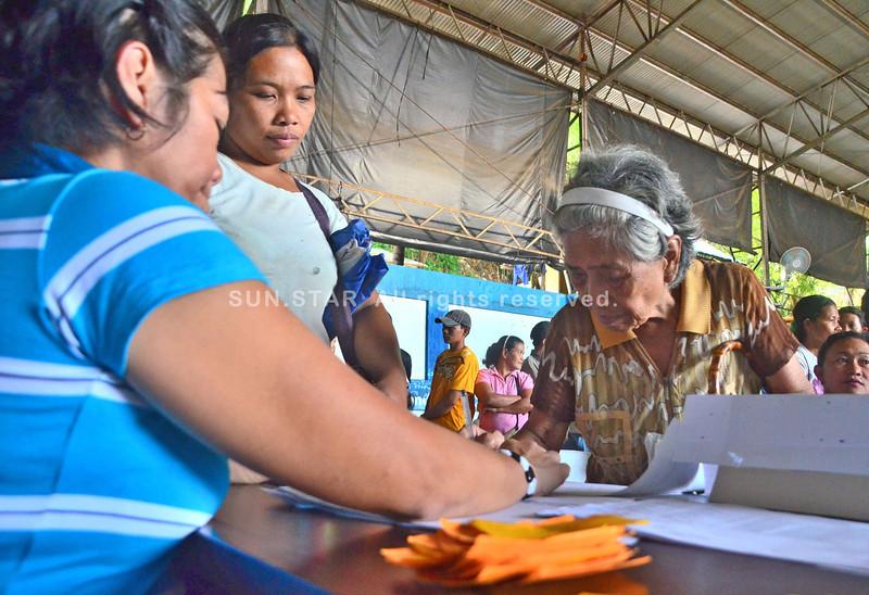 DAVAO. Si Fe Ecot, senior citizen sa Barangay 5-A mipirma aron madawat ang iyang hinabang kay usa siya sa biktima sa baha sa Lower Madapo niadtong milabay nga semana. (Seth delos Reyes)